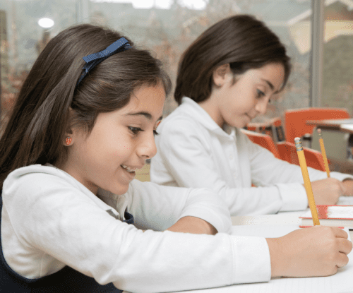 private school girls writing at their desk